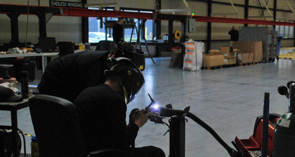 """alt=""""two employees working with the welding device"""""""